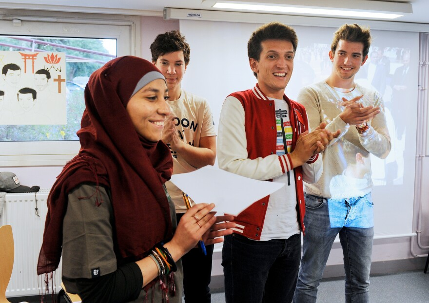 "Members of Coexister, (from left) Sabah Zouaghi, Ismael Medjoub, Samuel Grzybowski and Josselin Rieth, appear on June 2, 2014, in Le Mans, in western France. Members of the group took part in a 10-month ""interfaith tour"" to 40 countries to meet religious communities."