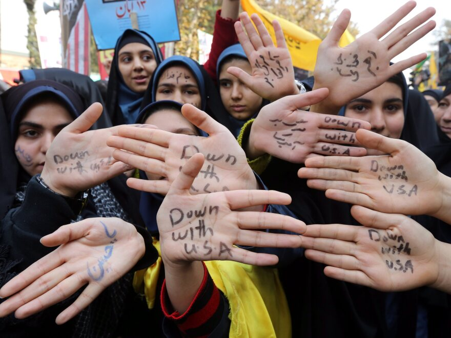 """Iranian girls show their hands, marked with the words """"Down with USA,"""" at Monday's demonstration in Tehran."""