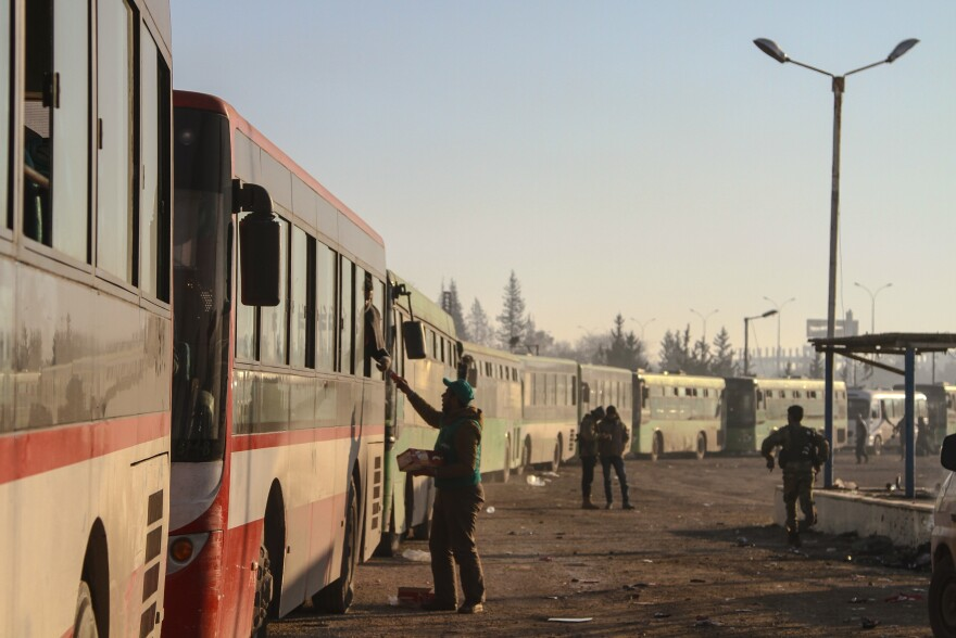 Civilians evacuated from east Aleppo arrive in Syria's Rashidin region on Monday. A series of cease-fire and evacuation deals have been negotiated, broken and renegotiated over the past few days.