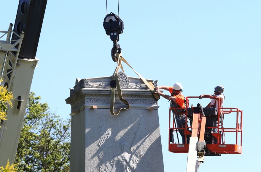 Workers attach straps to the granite top of the Confederate Memorial in Forest Park on June 8, 2017.