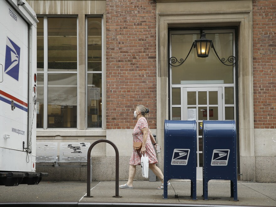 A woman walks past two mailboxes near a post office this week in New York City.