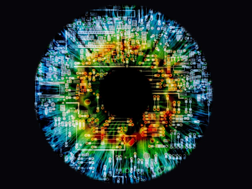 Composite image of a human eye and a circuit board.