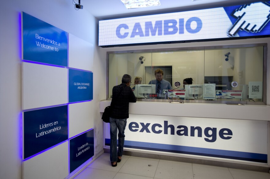 A man gets information about how to buy dollars at a foreign exchange business in Buenos Aires, Argentina, on Jan. 27.