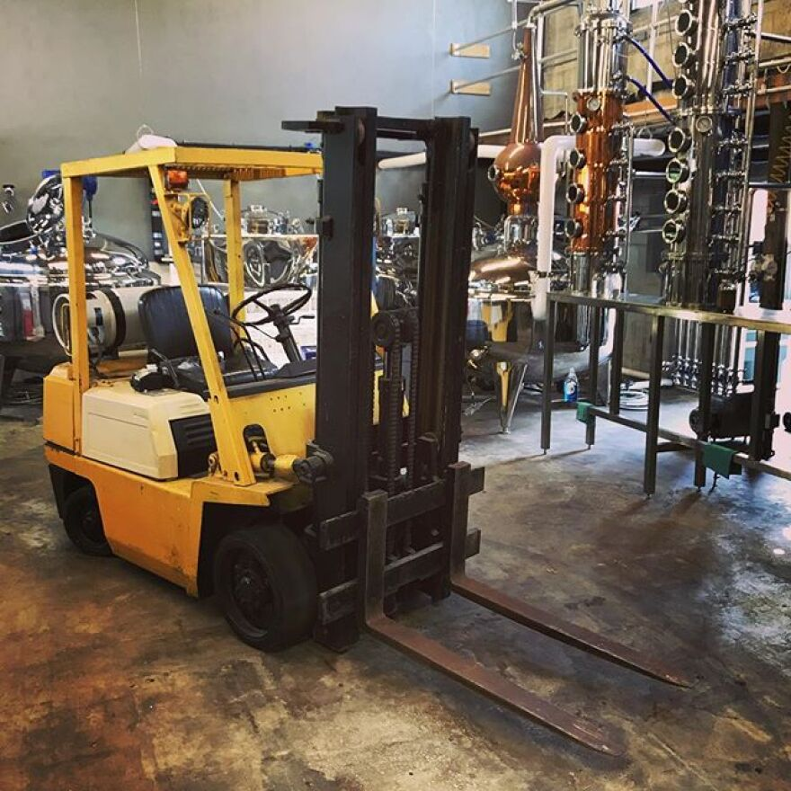 Large Machinery is ready for use in front of a row of metal objects used in the distilling process.