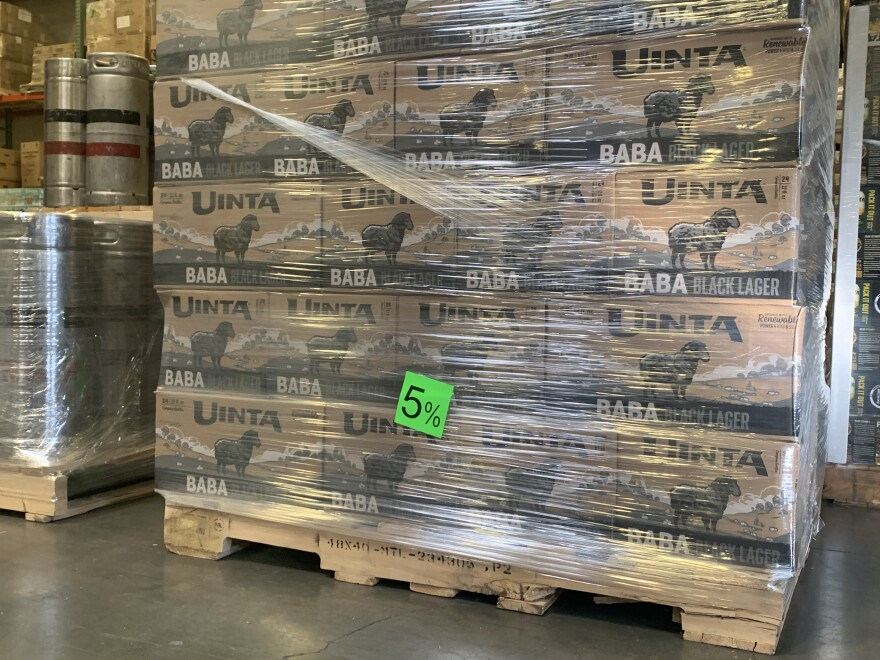 A pallet stacked with black lager beer affixed with a neon green 5% sticker.