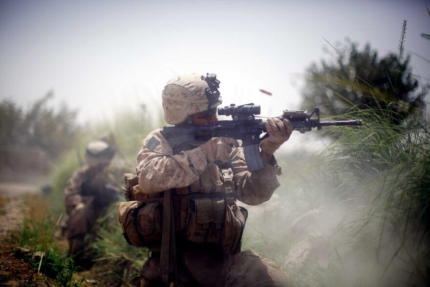 A U.S. Marine from the 2nd Marine Expeditionary Brigade, RCT 2nd Battalion, 8th Marines, Golf Company engages in a firefight on July 8, 2009, in Mian Poshteh, Afghanistan.