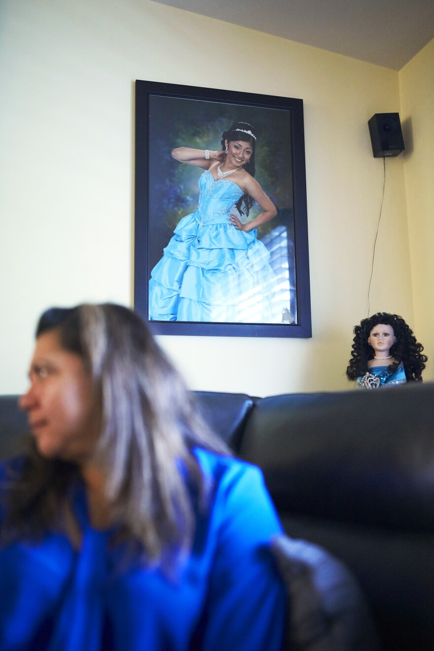 Araceli sits in front of a photo of her daughter. Alondra is part of the record number of Hispanics enrolling in college.