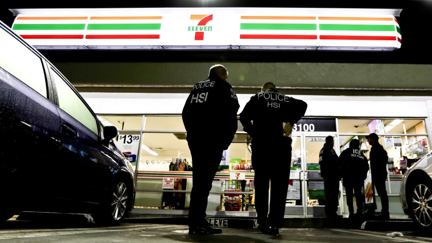 ICE agents serve an employment audit notice at a 7-Eleven in Los Angeles Wednesday. Agents raided 98 stores across the country.