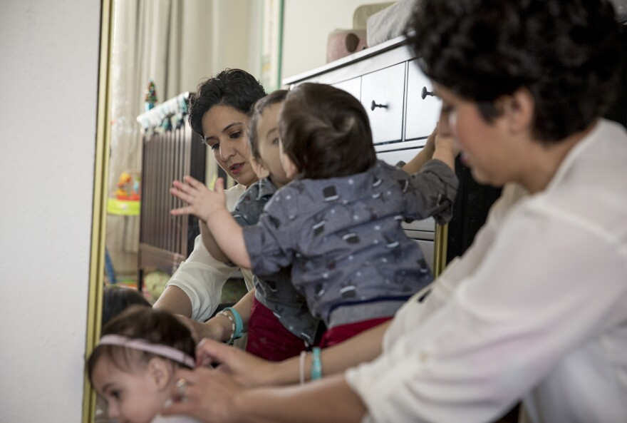 Leah Bahrencu is photographed with twins Lukas and Sorana, both 11 months, at their home in Austin, Texas.