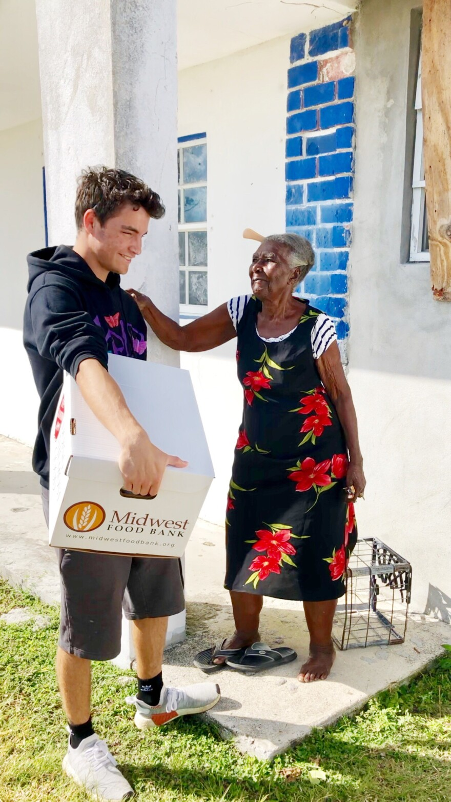 Young man with a box of food with smiling older woman.