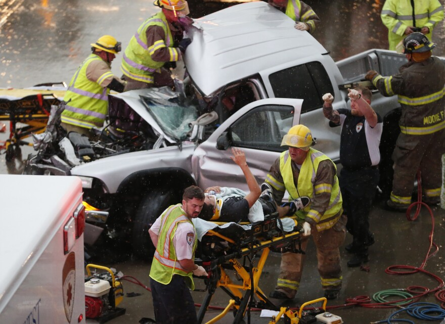 The driver of a truck that crashed during severe weather on Interstate 35 gestures to his rescuers after being cut from the truck in Moore, Okla., on Wednesday.