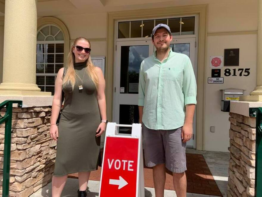 Woman and man stand next to Vote sign