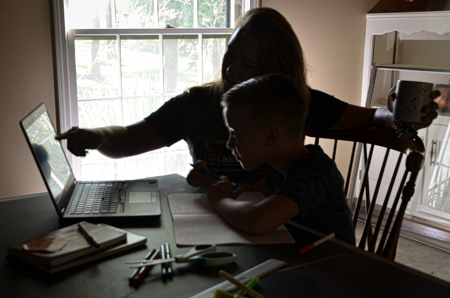 A young student sits at a desk with a laptop in his home with his mother pointing at the screen.