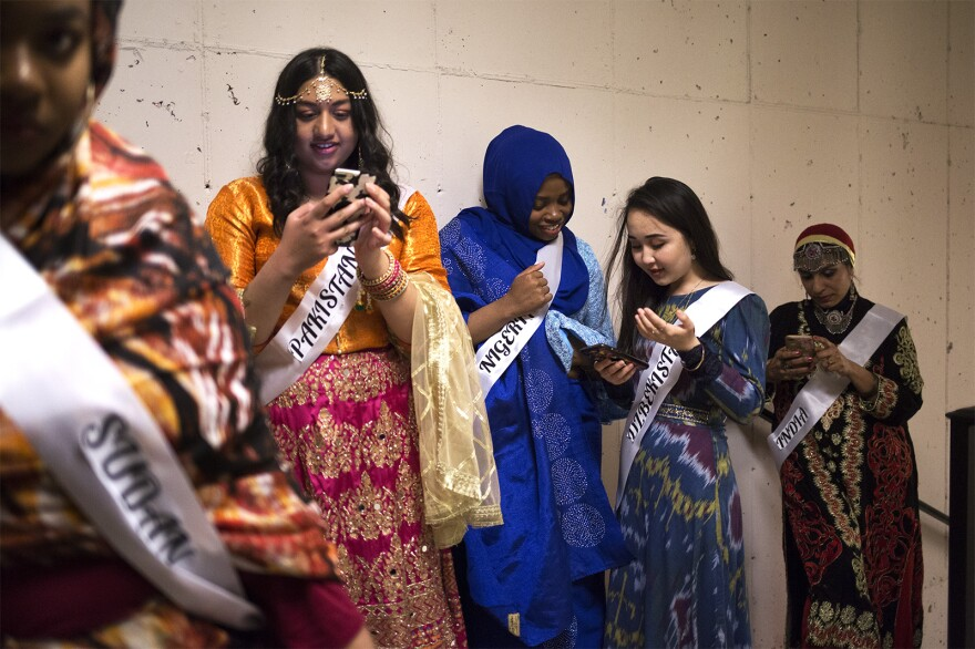 Models check their phones while waiting for the start of the Modest Muslim Women's Fashion Show. April 20, 2019