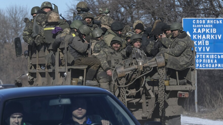 Ukrainian servicemen ride on a military vehicle as they leave the area of Debaltseve in eastern Ukraine Wednesday. The troops, some in columns, some in cars, began leaving the besieged town today.
