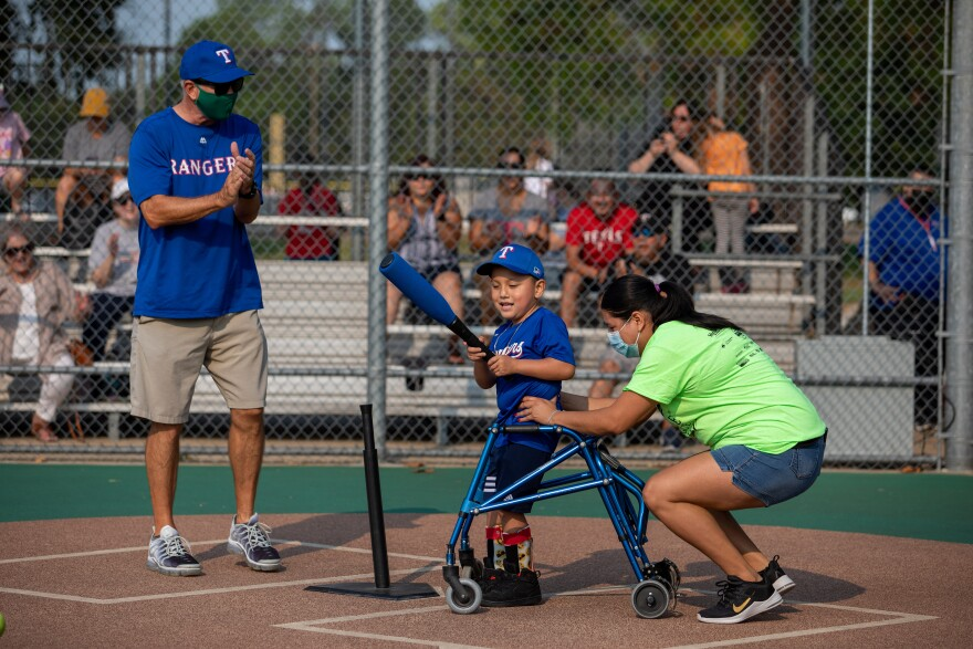 Jose Mendoza hits the ball with the bat, while his mother holds him, and the coach claps on Saturday's game.