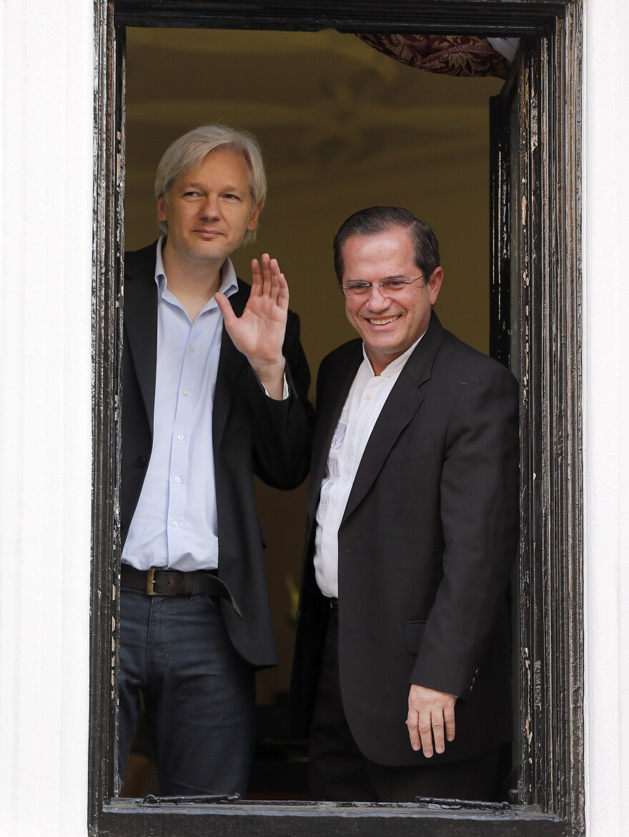 WikiLeaks founder Julian Assange (left) and Ecuadorian Foreign Minister Ricardo Patino appear on a window of the Ecuadorian Embassy in London on June 16. Assange has been living at the embassy for the past year. Patino announced Sunday that Ecuador would consider giving asylum to former NSA contractor Edward Snowden.