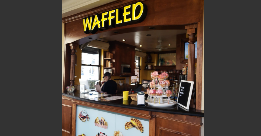 Photo of the inside of a restaurant advertising waffles