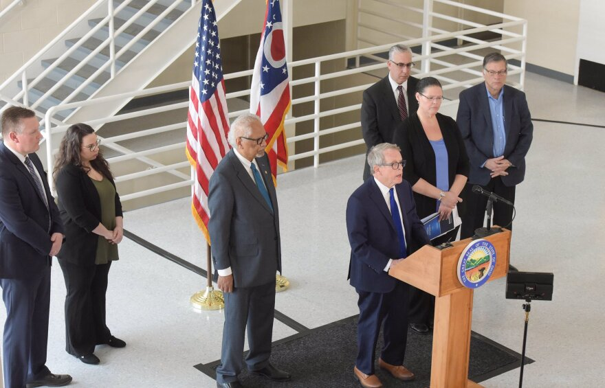Gov. Mike DeWine (center) speaks alongside members of the review group, including former prisons director Reginald Wilkinson (left) and current ODRC director Annette Chambers-Smith.
