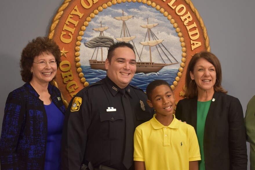 Big Brothers Big Sisters President/CEO Pam Iorio, left, poses with Tampa Police officer Joel McKee and Princeton, 10, at a press conference at TPD headquarters on Monday.