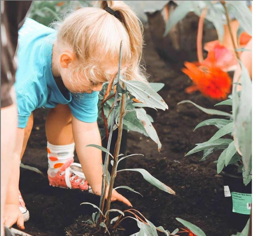 young girl with her hands in the dirt next to a flower