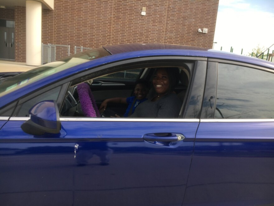Mom in driver's seat of car, with her son in the passenger side, looking out from stopped car to smile at reporter. The car's in front of the son's school.