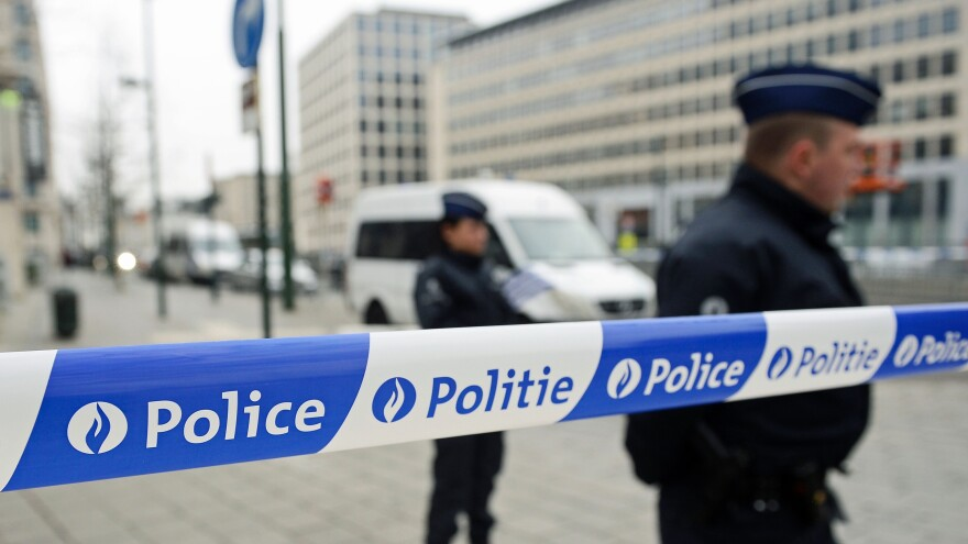 Police patrol outside the council chamber of Brussels on Thursday during ongoing investigations into the Paris and Brussels terrorist attacks. More than 30 people have been identified as being involved in a network behind the Paris attacks on Nov. 13, with links now established to this week's bombings in Brussels.
