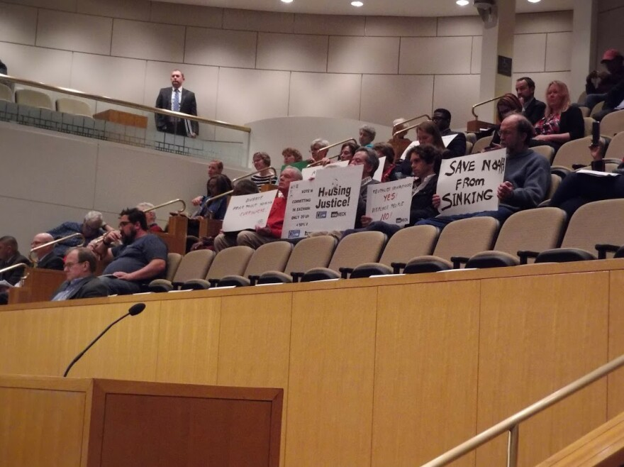 Affordable Housing advocates sat with signs at Monday's council meeting.