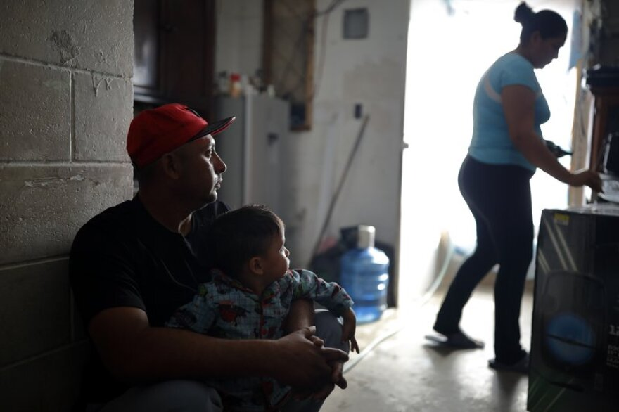 Juan Carlos Perla sits with his son, Joshua Perla, as his wife, Ruth Aracely Monroy, right, stands