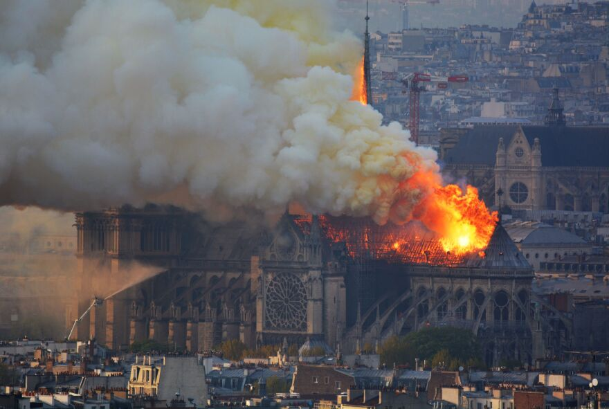 Smoke and flames rise from the landmark Notre Dame Cathedral in central Paris on Monday.