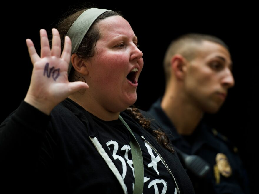"""A demonstrator raises her hand, on which the word """"no"""" is scrawled in black. She was one of many demonstrators clad in black who packed the Hart building Thursday in protest of Kavanaugh's nomination."""