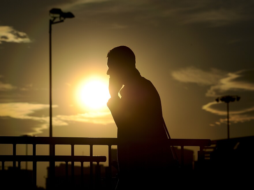 The sun sets as a visitor uses his mobile phone Monday during the opening day of the 2015 Mobile World Congress in Barcelona. <em>Wall Street Journal</em> reporter Ryan Knutson — interviewed from the conference Monday via Skype by NPR's Robert Siegel — says that for some smartphone users, Wi-Fi may be able to replace most of the functionality of a cellphone carrier.