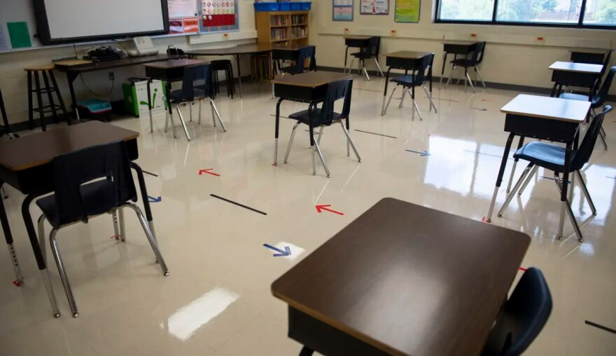 An empty classroom with arrows on the floor directing the flow of student traffic.