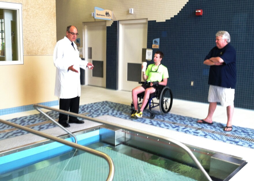Director of Haley's Polytrauma Center, Dr. Steven Scott, shows off the new treadmill pool for walking exercise to former patient Cory Remsburg and his father, Craig Remsburg.