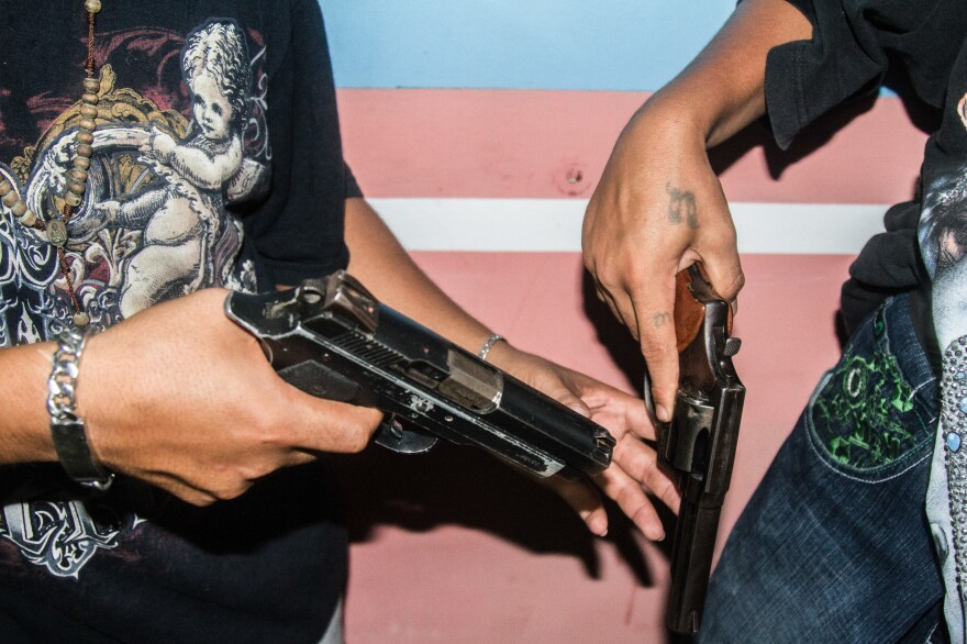 Before heading out on night patrol, gang members inspect their weapons in San Pedro Sula.