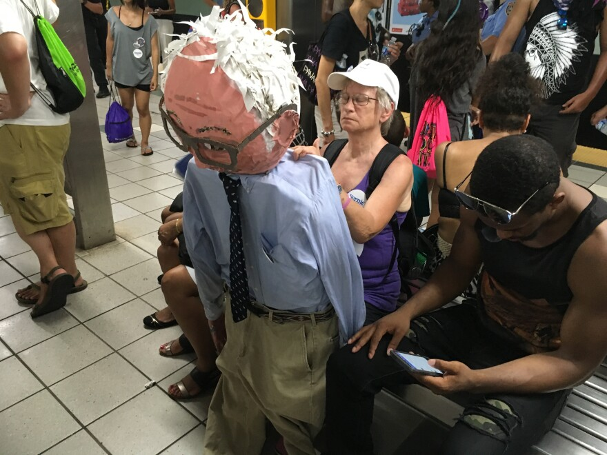 A woman holds a paper mache version of Bernie Sanders while waiting for the subway in Philadelphia.