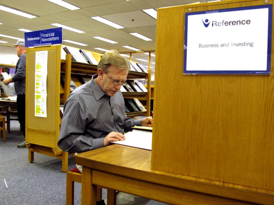 Ray Meyer researches potential employers at the library near his home in Kirkwood, Mo. Meyer recently started doing temp work but is still searching for a job in banking.