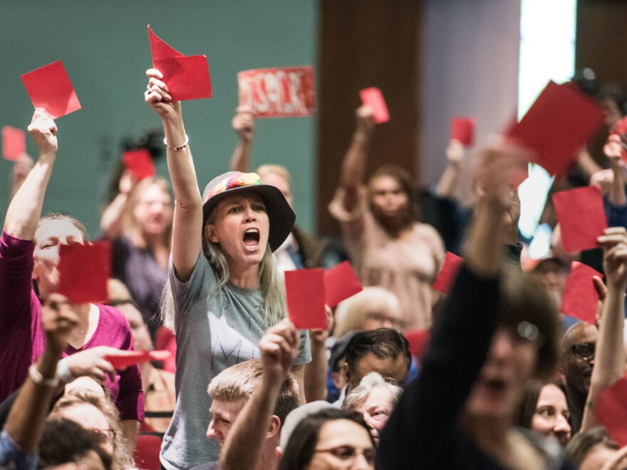 Constituents hold up red signs of disagreement with Sen. Lindsey Graham during a town hall meeting today in Columbia, S.C.