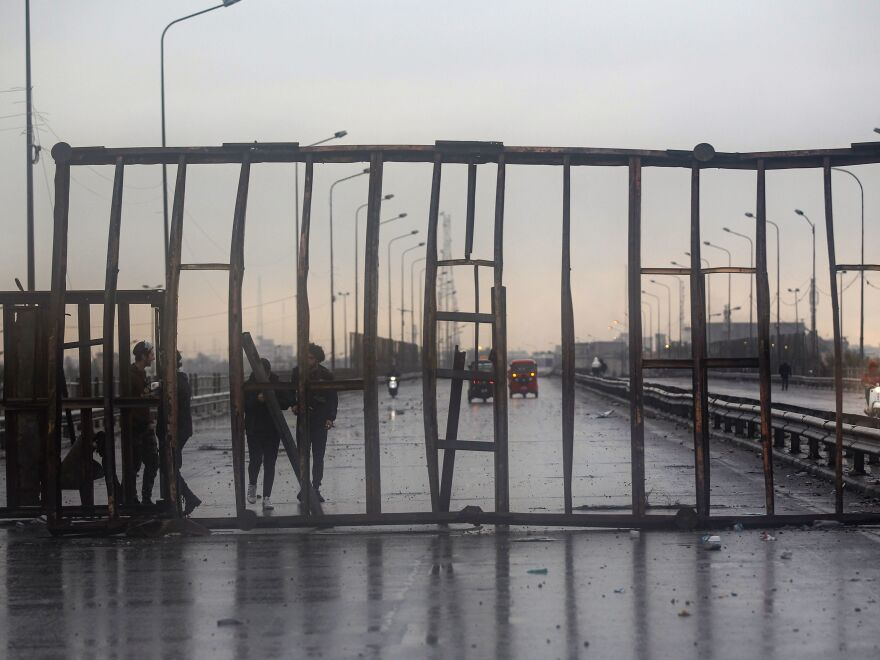 Iraqi protesters stand near makeshift barriers and burning tires on Mohammad al-Qasim highway in east Baghdad on Wednesday.