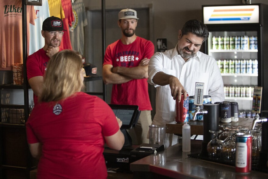 A Zilker Brewing Company employee sells state Rep. Eddie Rodriguez beer to go.