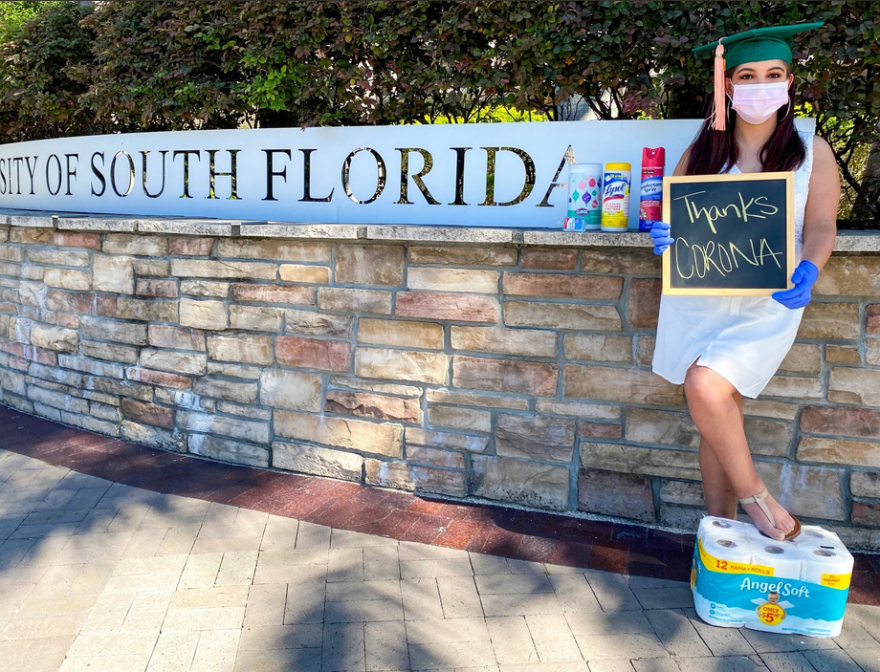 a young woman holds a sign thanking Corona while resting her foot on a bunch of toilet paper in front of a USF sign
