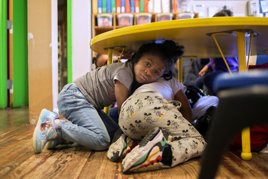 Justice Buress, 4, demonstrates how she hides under a table during a drill at Little Explorers Learning Center in St. Louis. Day care director Tess Trice carries out monthly drills to train the children to get on the f loor when they hear gunfire.