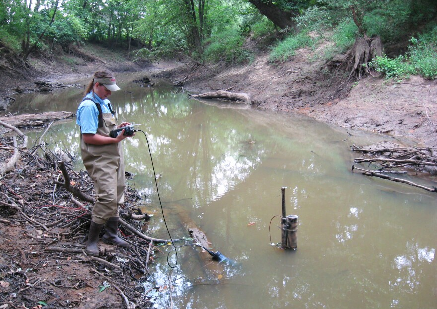 Lynn Milberg measures the dissolved oxygen concentration of the water at Little Dry Wood Creek in Vernon County, Mo. Nutrient runoff promotes the growth of algae, which can cause oxygen levels to plummet.