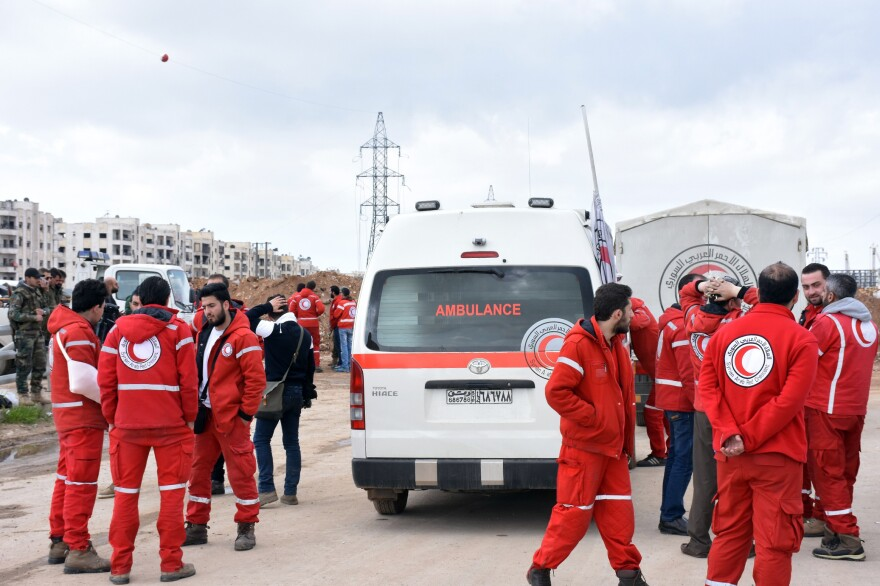 Syrian Red Crescent paramedics wait on Friday for the buses evacuating civilians from the government-held villages of Fuaa and Kafraya, on a highway in eastern Aleppo.