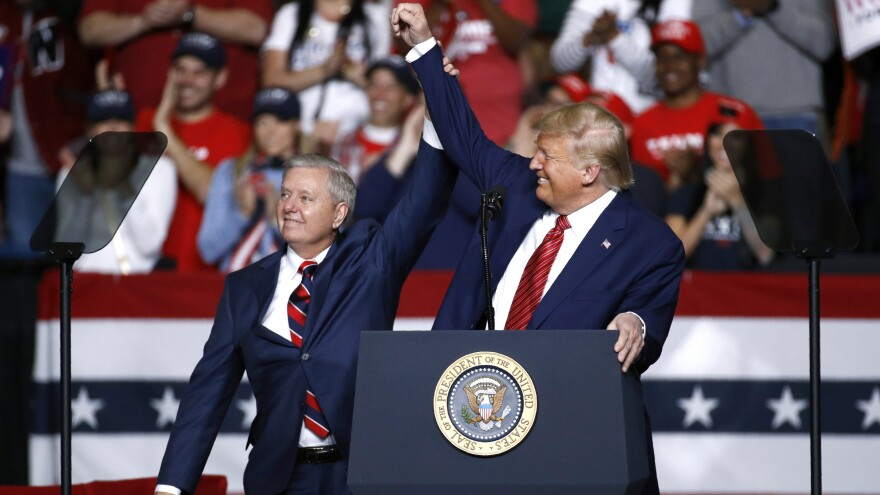 Sen. Lindsey Graham, R-S.C., stands onstage with President Donald Trump during a Feb. 28 campaign rally, in North Charleston, S.C. His allegiance to Trump has left some moderate voters feeling snubbed and switching allegiances ahead to Democrat Jaime Harrison.