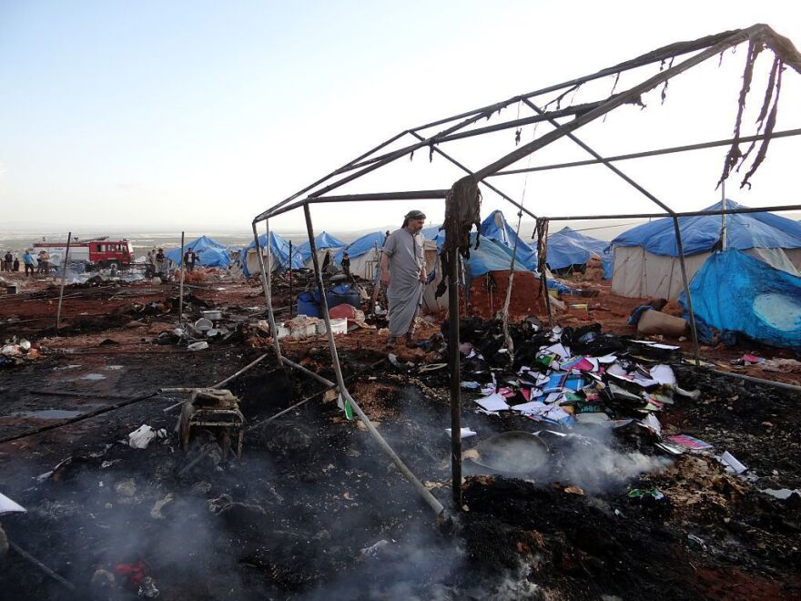People inspect the damage after an airstrike hit a refugee camp in Idlib province on Thursday.