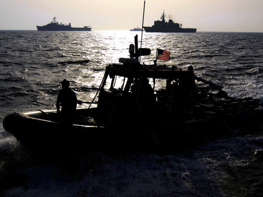 A U.S. Navy speedboat passes in front of multinational military ships in the Persian Gulf on Sept. 21 as part of the military exercise. If attacked, Iran says it will close the Strait of Hormuz, which is a crucial shipping route.