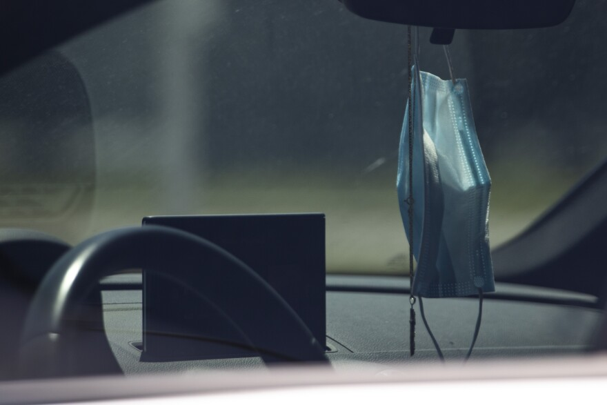 A face mask hangs from the rearview mirror of a parked car during the coronavirus pandemic.