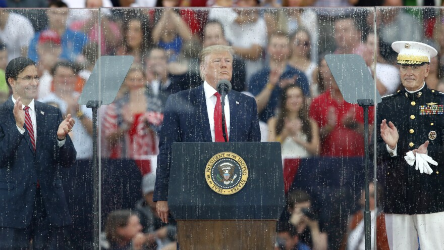 President Trump speaks behind rain-streaked glass during the Independence Day celebration in front of the Lincoln Memorial.