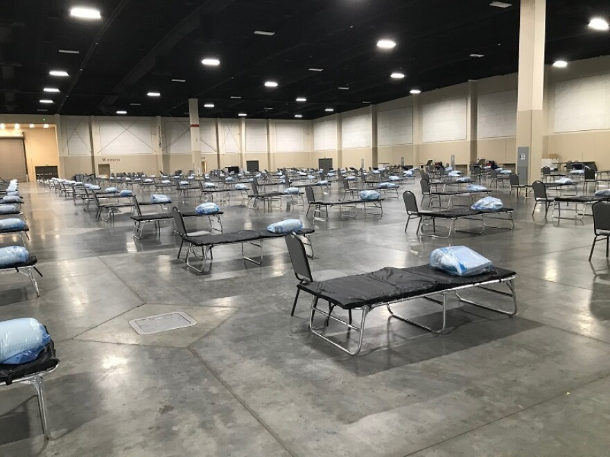 Photo of rows of cots in a large warehouse.